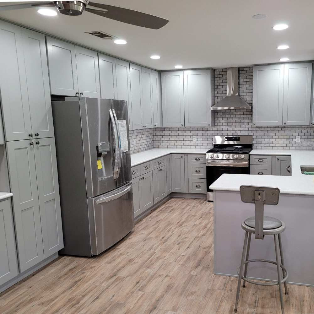 Clean Gray shaker style cabinets with multi -gray subway tile backsplash and new appliances