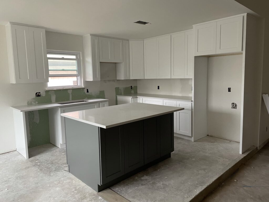 Modern Kitchen With White Shaker Cabinets and Grey Shaker Island with white quartz countertop